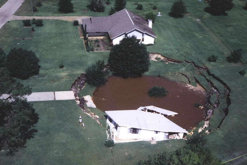A sinkhole swallows a house, trees and anything else in its way