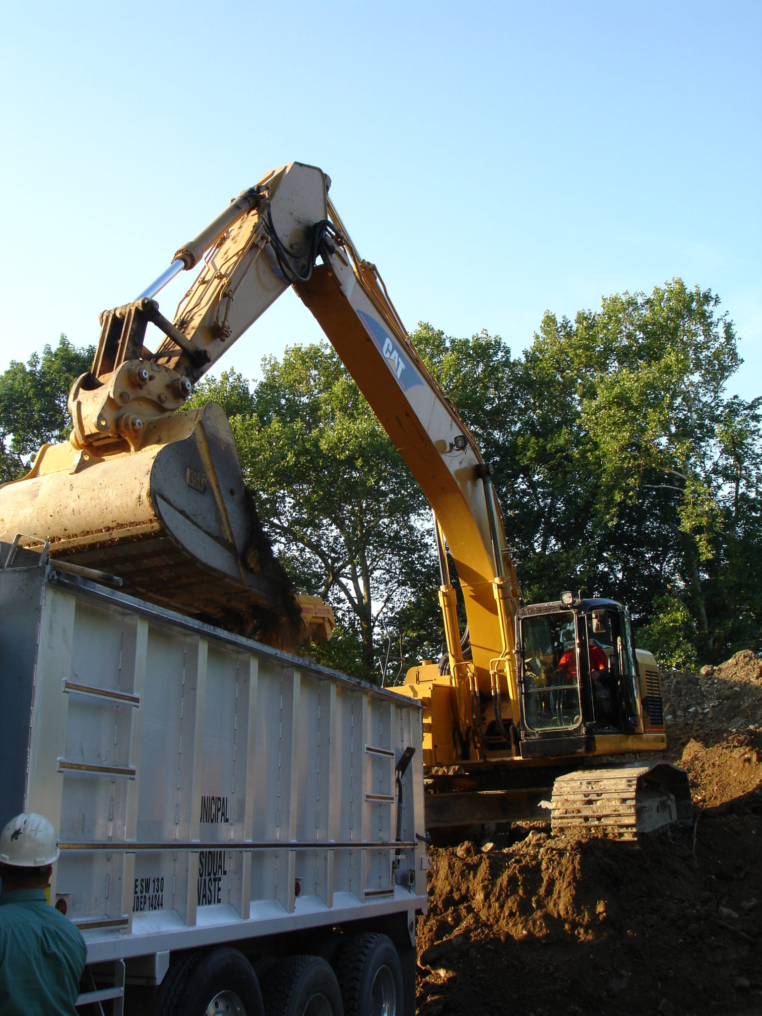 A digger removes Soil to Dispose of in the appropriate way